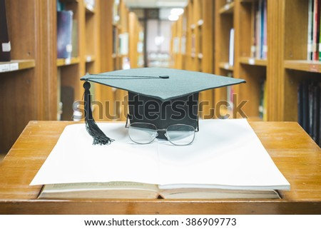 graduation cap with glasses on open book,Education concept - stock photo