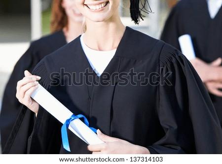 graduation girl holding her diploma - stock photo