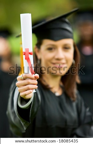 graduation girl holding her diploma with pride - stock photo