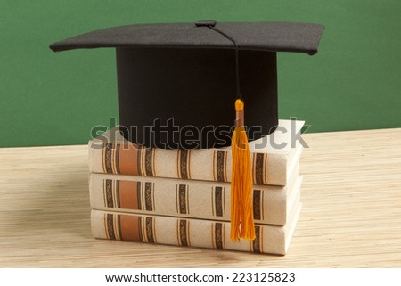 Graduation hat with old book on the background of school board - stock photo