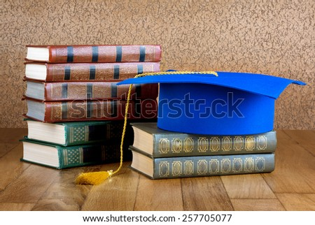 Graduation mortarboard on top of stack of books on wooden background of wall - stock photo