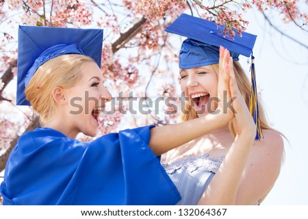 Graduation Pretty Blonde women excited and celebrating with a high five! - stock photo