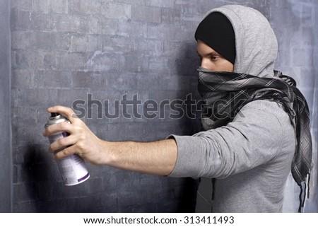 Graffiti man in hooded shirt and face mask spraying brick wall by aerosol can. - stock photo