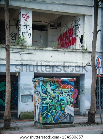 Grafitti on power box next to abandoned house - stock photo