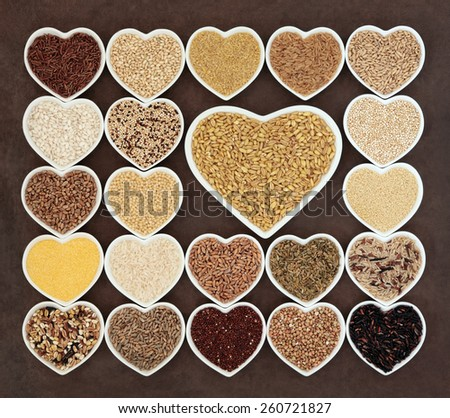 Grain and cereal food selection in heart shaped porcelain bowls over lokta paper background. Kamut khorasan wheat in large dish. - stock photo