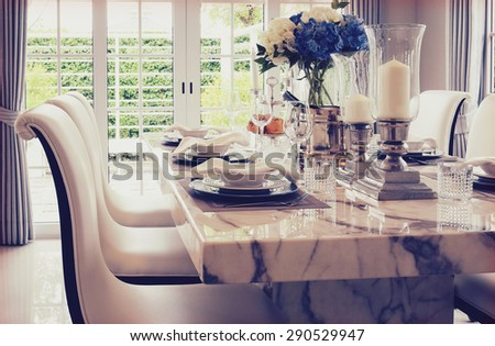 grain and vintage effect photo of dining table and comfortable chairs with elegant table setting - stock photo