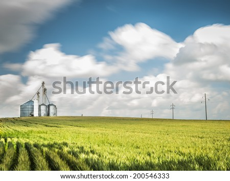 Grain Elevator on Hill With Cloud Motion - stock photo