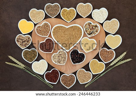 Grain food selection on a heart shaped wooden board and in porcelain bowls with wheat ears over lokta paper background. - stock photo