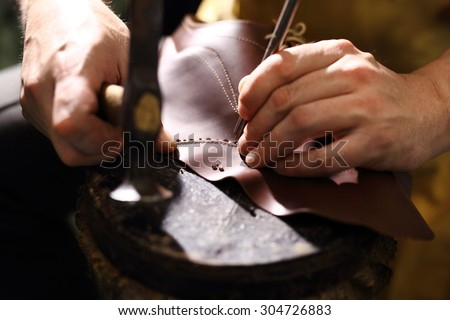 Grain leather. Shoemaker performs shoes in the studio craft - stock photo