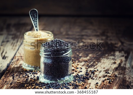 Grains of black mustard and mustard sauce, selective focus - stock photo