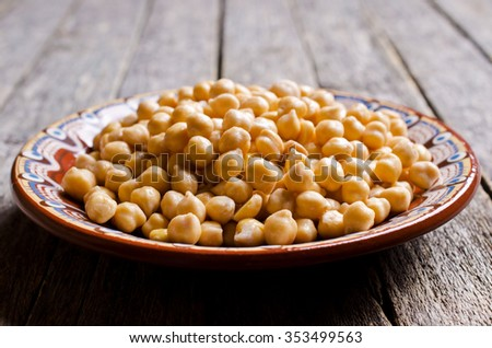 Grains of raw chickpeas in a pot on a wooden surface. Selective focus. - stock photo