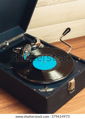 Gramophone with a vinyl record on wooden table - stock photo