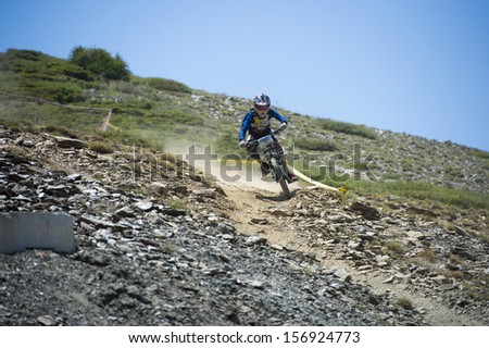 "GRANADA, SPAIN - JUNE 30: Unknown racer on the competition of the mountain downhill bike ""Bull bikes Cup DH 2013, Sierra Nevada "" on June 30, 2013 in Granada, Spain - stock photo"