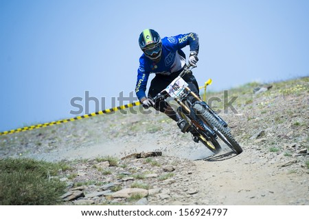 """GRANADA, SPAIN - JUNE 30: Unknown racer on the competition of the mountain downhill bike """"Bull bikes Cup DH 2013, Sierra Nevada """" on June 30, 2013 in Granada, Spain - stock photo"""