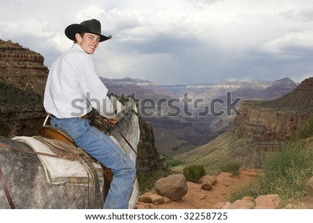 Grand Canyon National Park trail guide on muleback traveling Bright Angel trail descending South Rim.  Scenic overlook. - stock photo