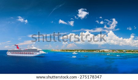 "GRAND CAYMAN, CAYMAN ISLANDS - 14:00. JUNE 5, 2008: Carnival ""Triumph"" cruise ship tendered next to the tropical island. Over 3,500 guests went out to visit beautiful port. - stock photo"