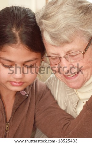 Grand daughter and grand mother with faces close together - stock photo