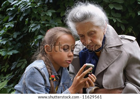 Grand daughter and her grand mother dial mobile phone - stock photo