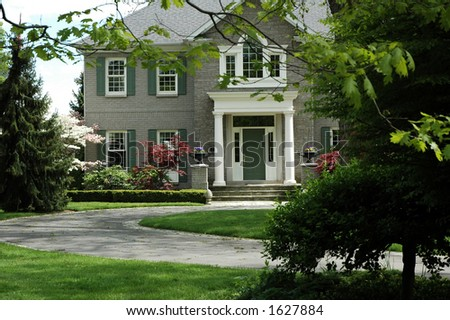 Grand house with green shutters, white pillars and curved driveway - stock photo