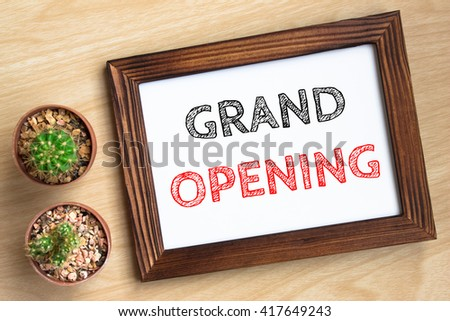 grand opening, text message on wood frame board on wood table / business concept / Top view - stock photo