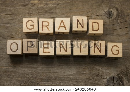 Grand Opening text on a wooden cubes on a wooden background - stock photo