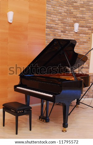 Grand piano with bench in the studio - stock photo