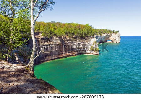 Grand Portal Point Pictured Rocks National Lakeshore near Munising, in the Upper Peninsula of Michigan. A wispy waterfall can be spied spilling over the sandstone rock face and into Lake Superior - stock photo