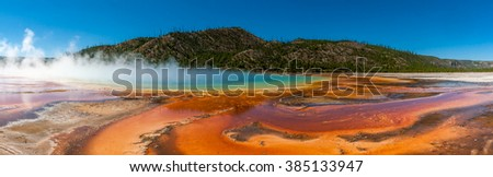 Grand Prismatic Spring - Beautiful cerulean geyser surrounded by colorful layers of bacteria, against cloudy blue sky in Yellowstone National Park,USA - stock photo
