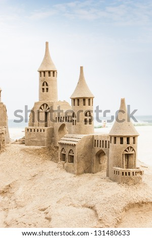 Grand sandcastle on the beach during a summer day - stock photo