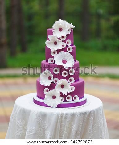 Grand violet wedding cake with white sugar paste flowers - stock photo