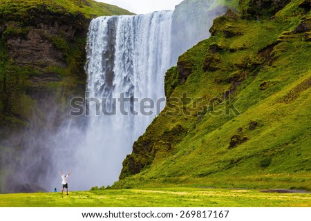 Grand waterfall Skogafoss in Iceland. Tourist in shirt and bandana threw up his hands with delight the beauty of nature - stock photo