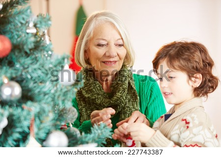 Grandchild and grandmother decorating together the christmas tree - stock photo