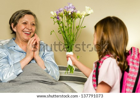 Grandchild giving bouquet of flowers to grandmother lying in bed - stock photo