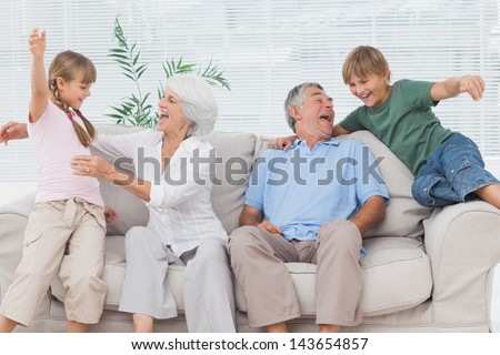 Grandchildren jumping on couch with their grandparents in the living room - stock photo