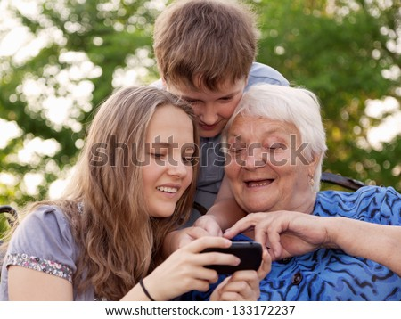 grandchilds help the grandmother to master the smart phone - stock photo