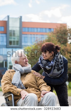 Granddaughter and disabled grandpa in a wheelchair - stock photo