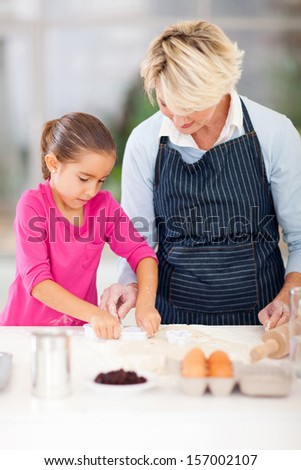 granddaughter and grandmother baking cookies together in kitchen - stock photo
