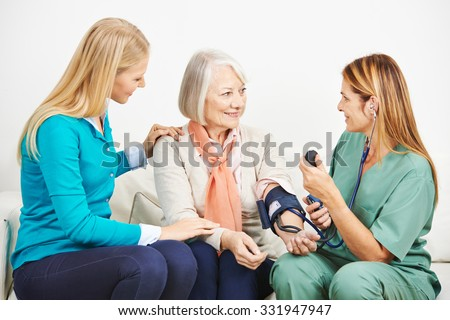 Granddaughter and senior woman with nurse doing blood pressure monitoring - stock photo