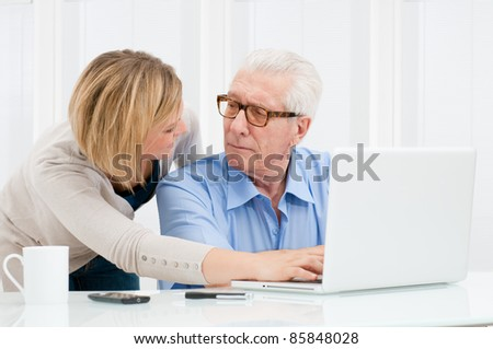 Granddaughter helping her grandfather at computer laptop - stock photo