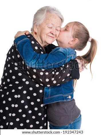 Granddaughter kissing her grandmother on white background - stock photo