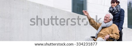 Granddaughter spending day with grandfather in wheelchair - stock photo