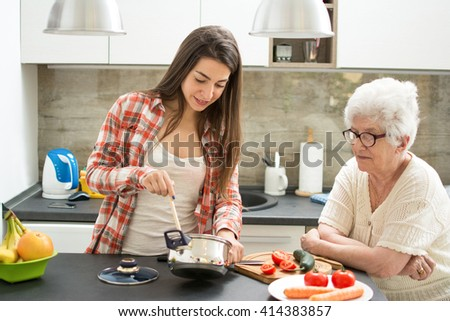 Granddaughter with grandmother cooking in the kitchen. - stock photo