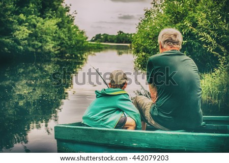 grandfather and boy fishing together. HDR. boy and an old man sitting in a boat with a fishing rod. view from the back - stock photo