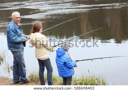 Grandfather and grandchildren are fishing. Grandfather and grandchild - stock photo