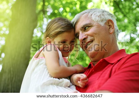 Grandfather and granddaughter enjoying in the park.  - stock photo