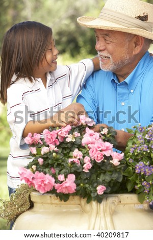Grandfather And Granddaughter Gardening Together - stock photo