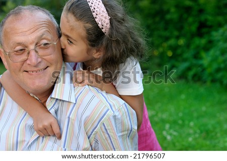 Grandfather and granddaughter having fun outdoors - stock photo