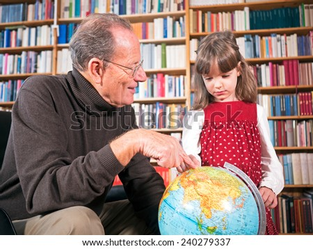 Grandfather and granddaughter looking at a globe - stock photo