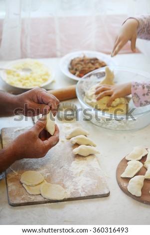 Grandfather and granddaughter preparing dumplings together. hand mold dumplings with potatoes, photo toning Pastel.photo toning Pastel - stock photo