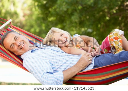 Grandfather And Granddaughter Relaxing In Hammock - stock photo
